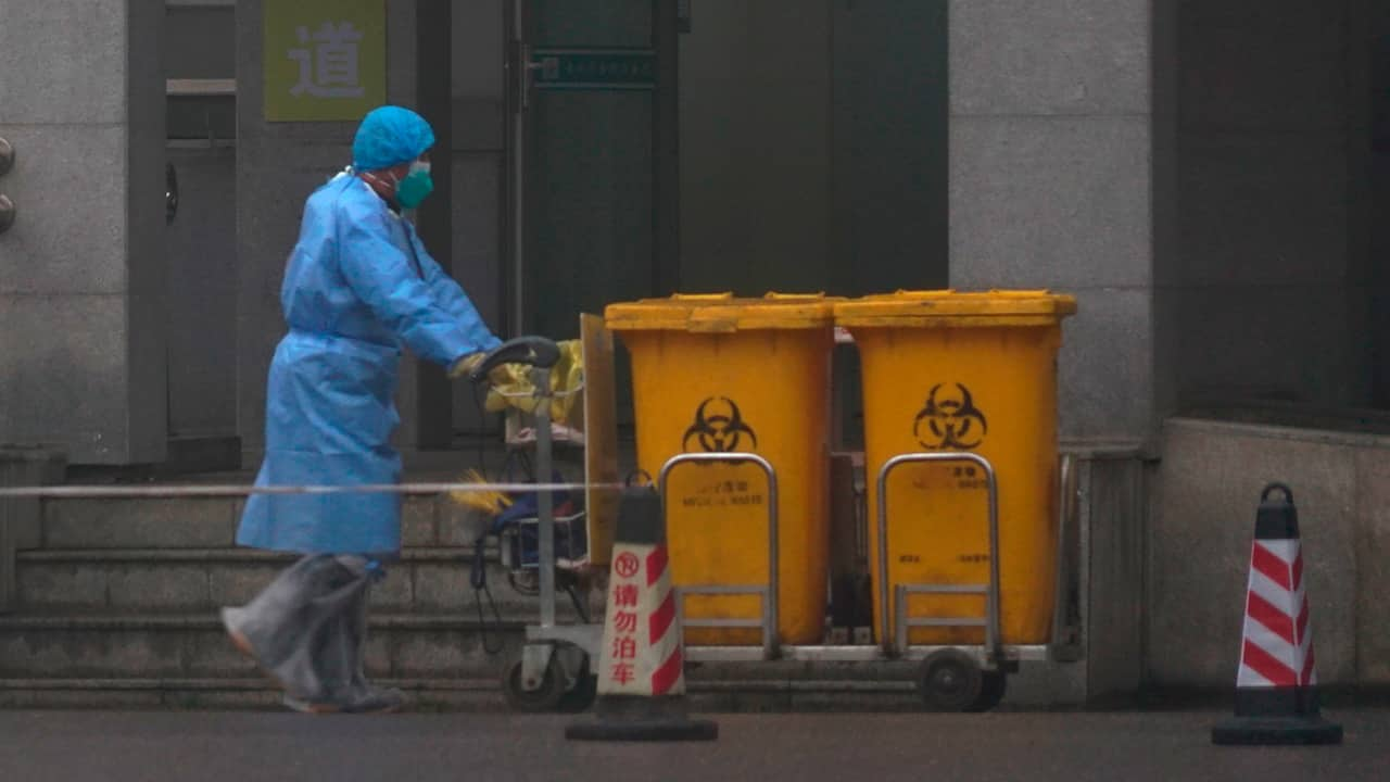 Photo of staff members moving bio-waste containers in China