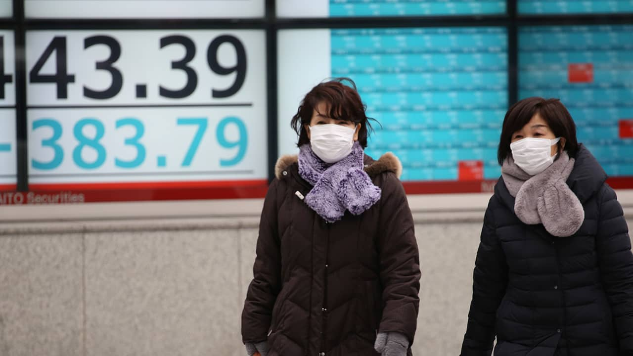 Photo of people walking by an electronic stock board of a securities firm in Tokyo