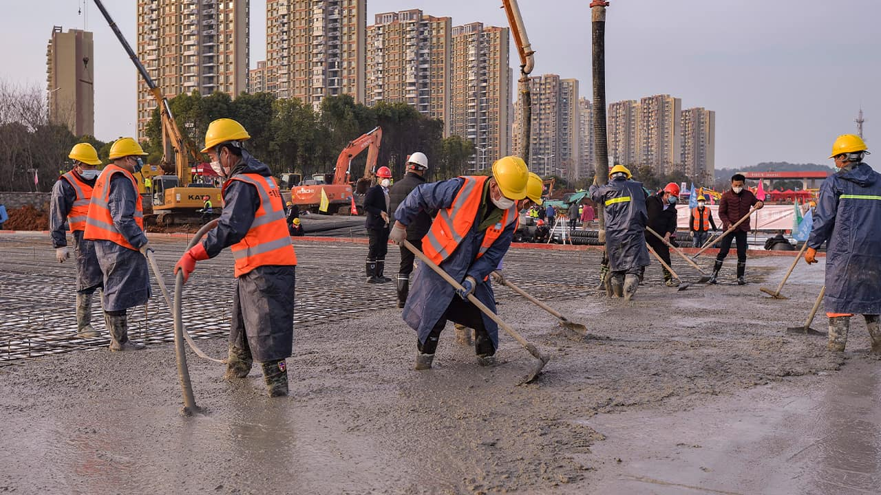 Photo of construction workers at the site of a temporary hospital