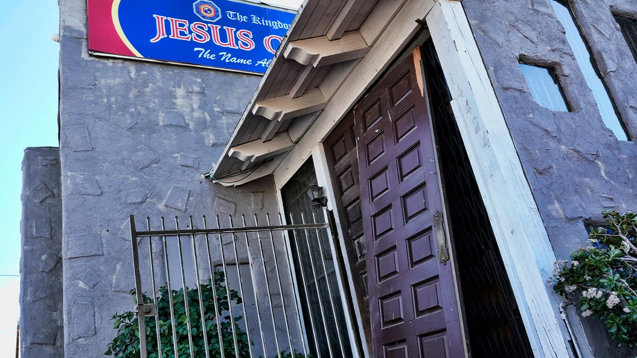 Photo of a smashed in door at the entrance of the Kingdom of Jesus Christ Church