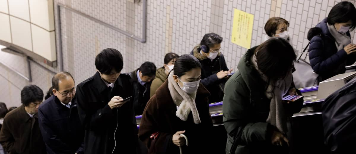 Photo of commuters, some with face masks on, riding an escalator during rush hours in Tokyo