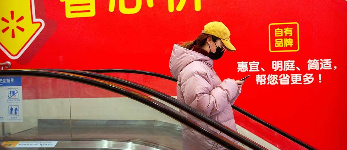 Photo of a woman wearing a face mask as she rides an escalator at a supermarket in Beijing