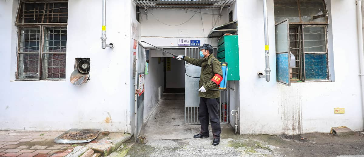 Photo of a government worker spraying disinfectant on a residential building in Wuhan