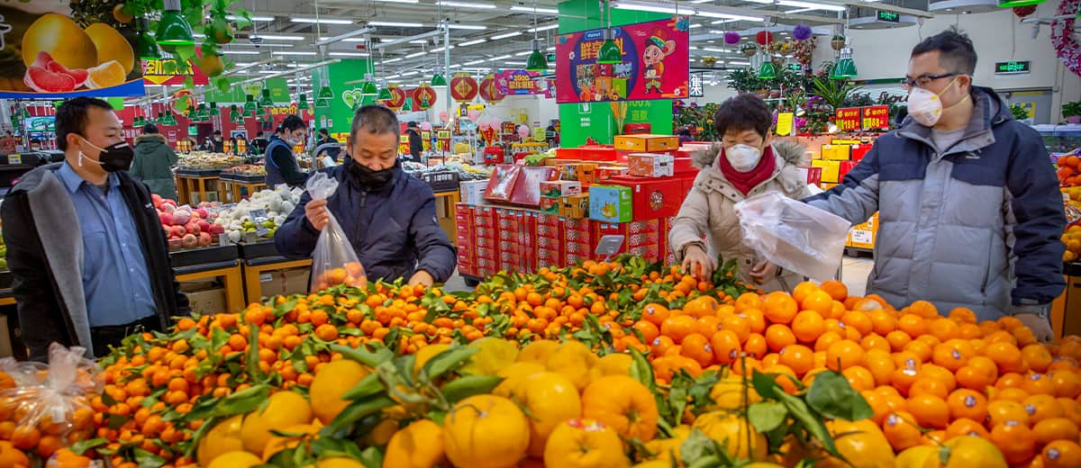 Photo of people wearing face masks as they shop for produce at a supermarket in Beijing