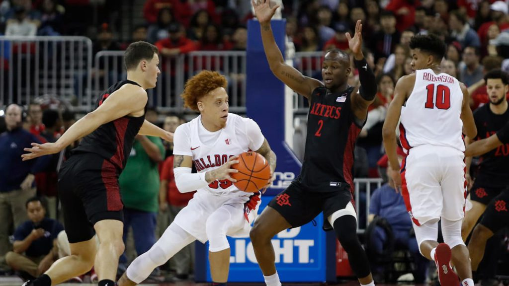 Photo of San Diego State players surrounding Fresno State's Noah Blackwell