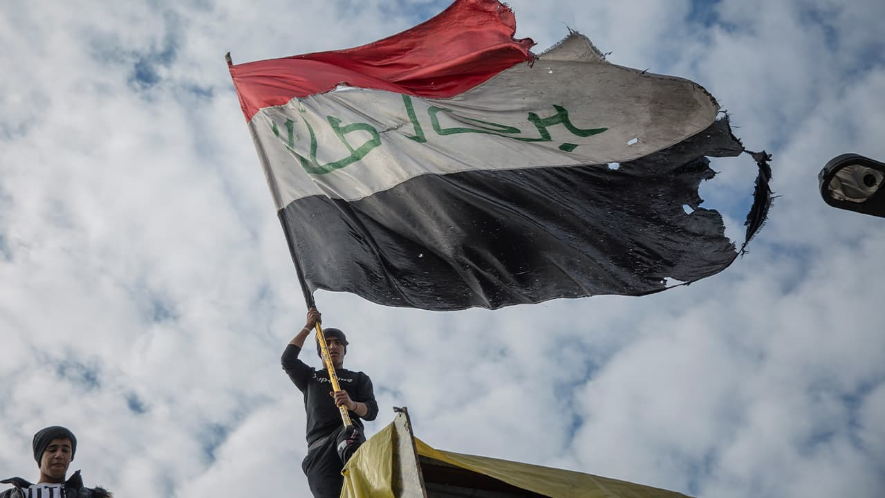 Photo of protesters flying an Iraqi flag