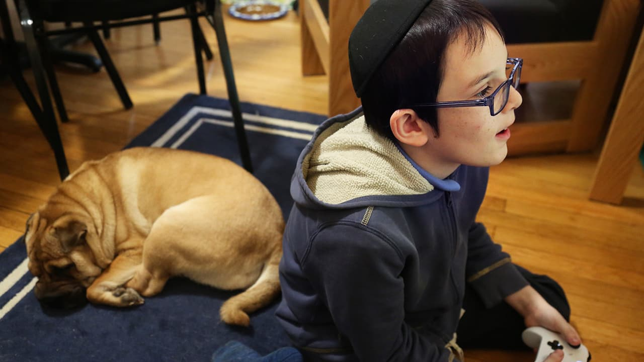 Photo of Gavriel Menachem Blum, 10, playing a video game before Shabbat dinner