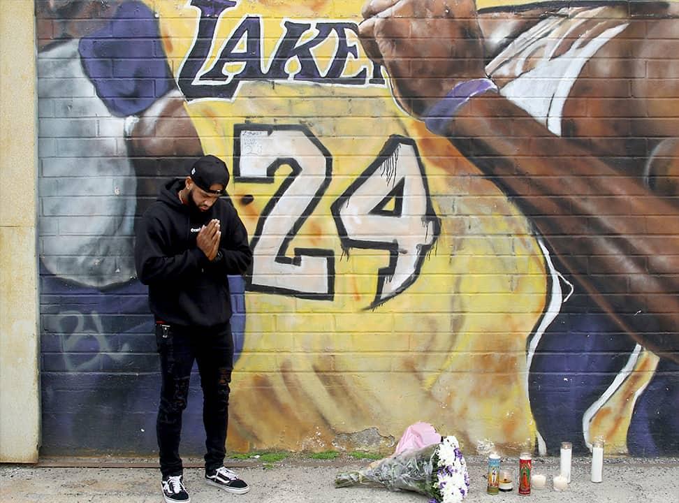 Photo of a man praying at a mural of Kobe Bryant in LA