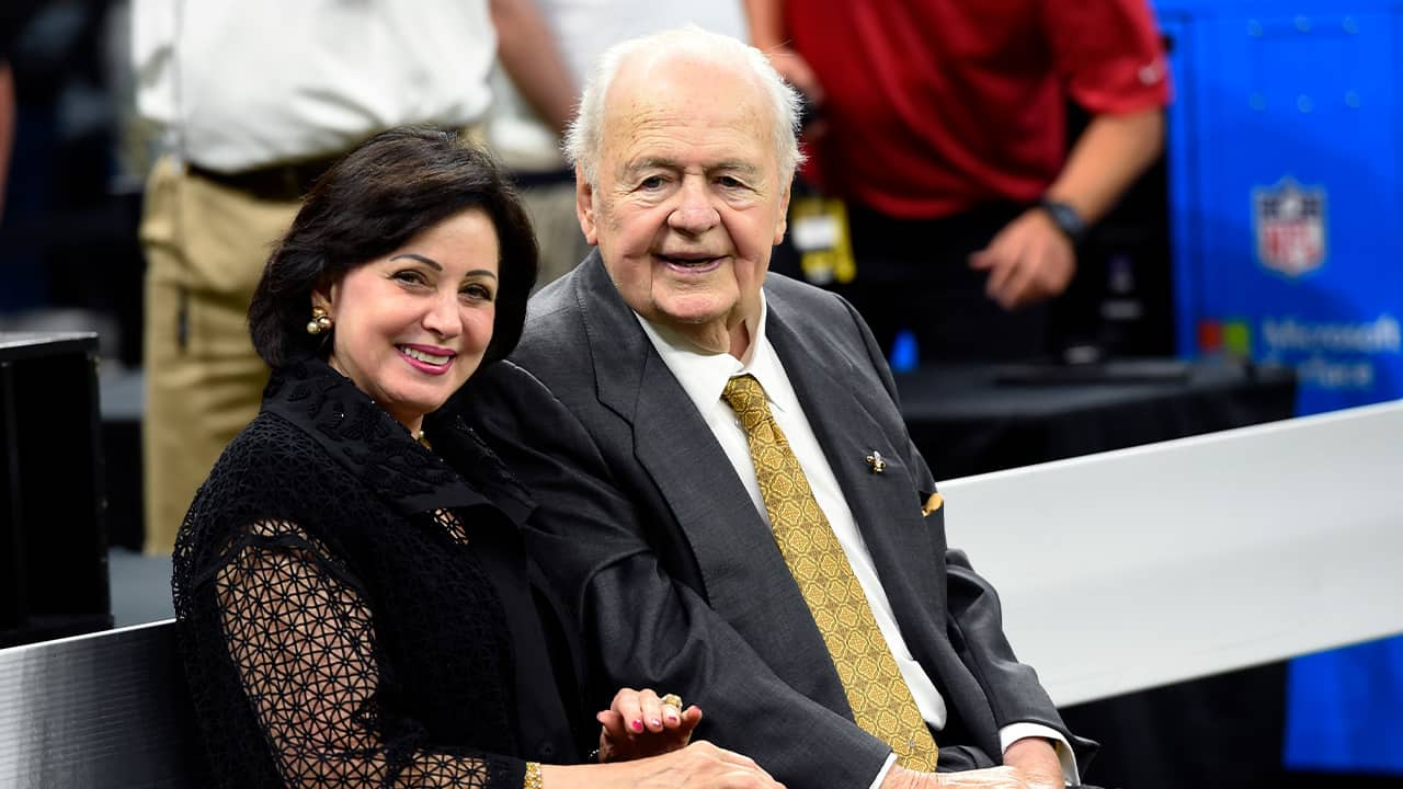 Photo of New Orleans Saints owner Tom Benson sits on the sideline with his wife, Gayle Benson