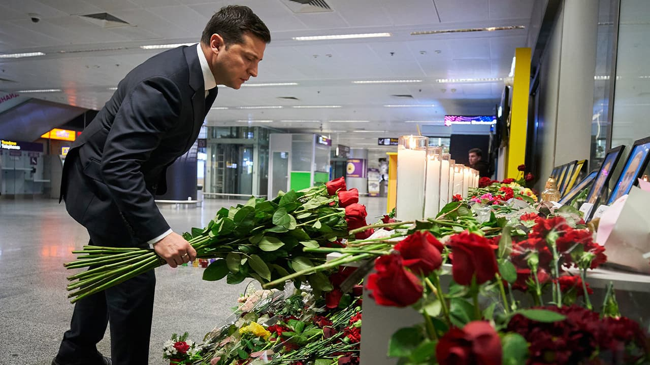 Photo of a man laying flowers at a memorial of the flight crew members of the Ukrainian 737-800 plane that crashed on the outskirts of Tehran