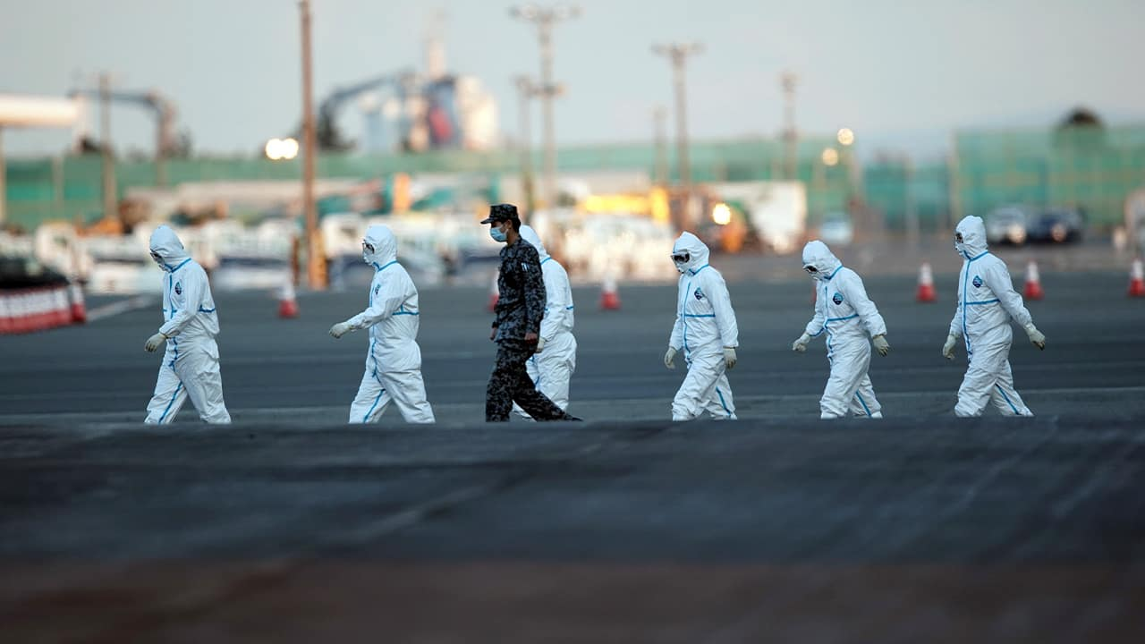 Photo of officials in protective suits