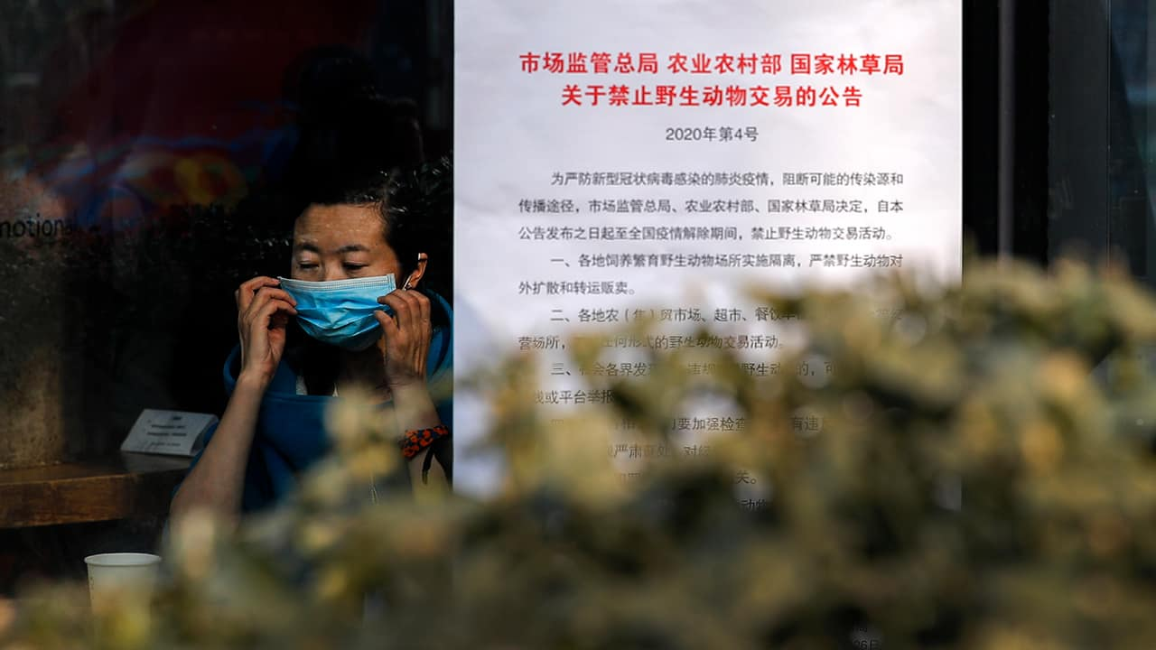 Photo of a woman putting on a mask near a notice board