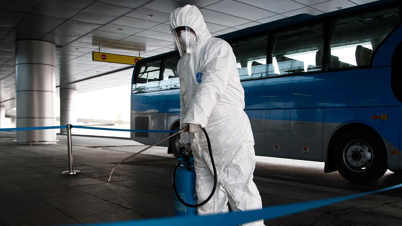 Photo of a worker disinfecting a ground transportation area in North Korea