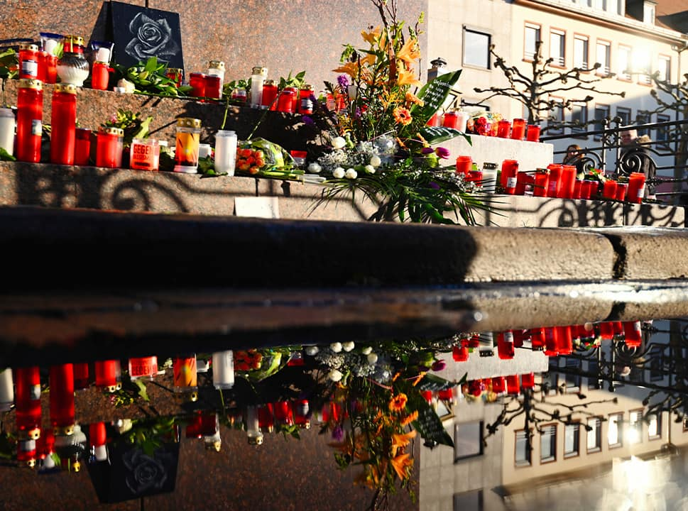 Photo of flowers and candles set around a monument for the brothers Grimm