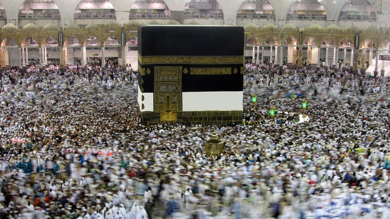 Photo of Muslim pilgrams walking around the Kabaa