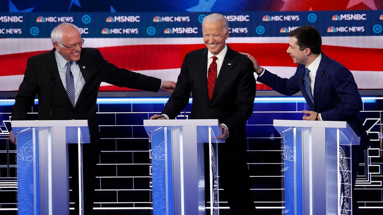 Photo of Democratic presidential candidates Sen. Bernie Sanders, I-Vt., left, and former South Bend Mayor Pete Buttigieg, right, reaching for former Vice President Joe Biden
