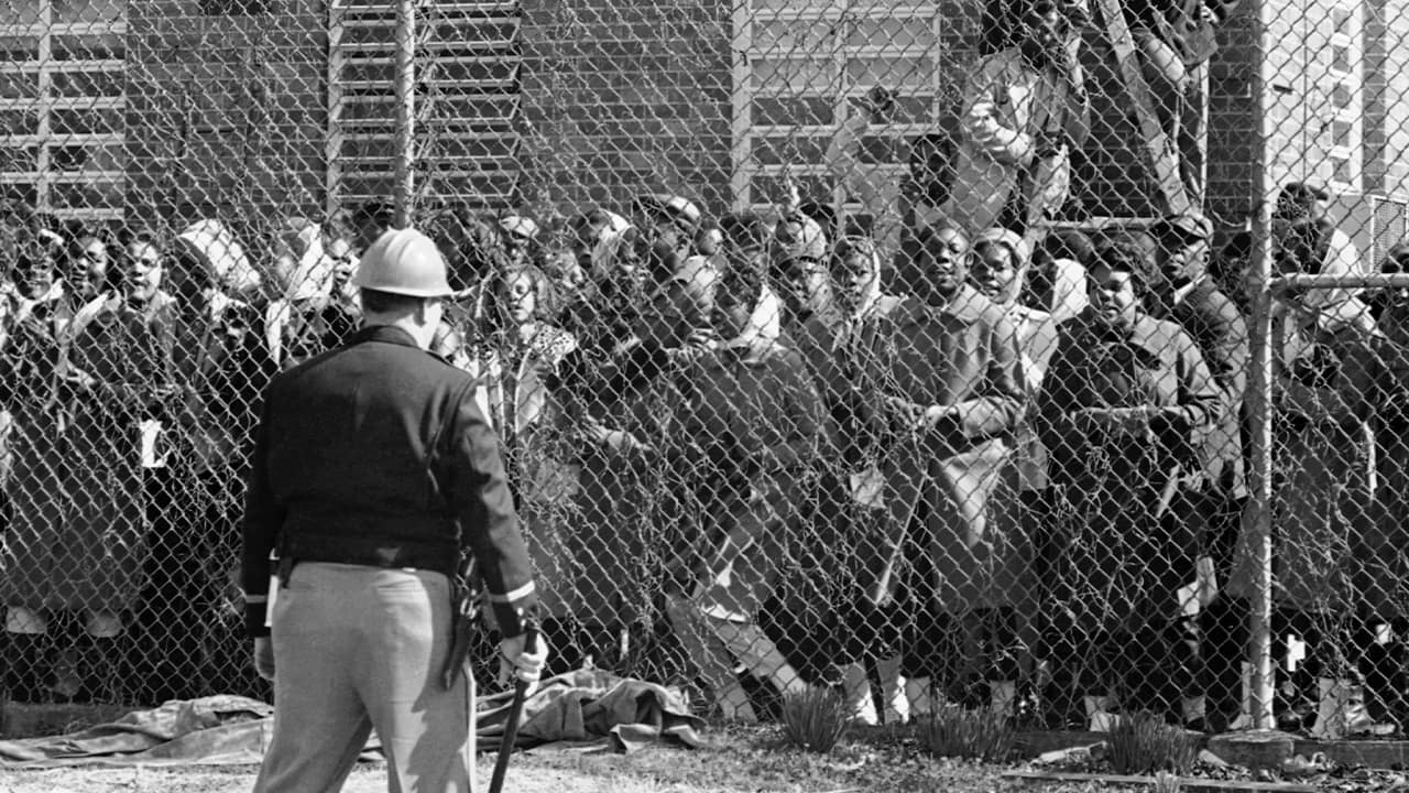 Photo of a policeman outside a fence surrounding the Perry County Jail in Marion, Ala. in 1965