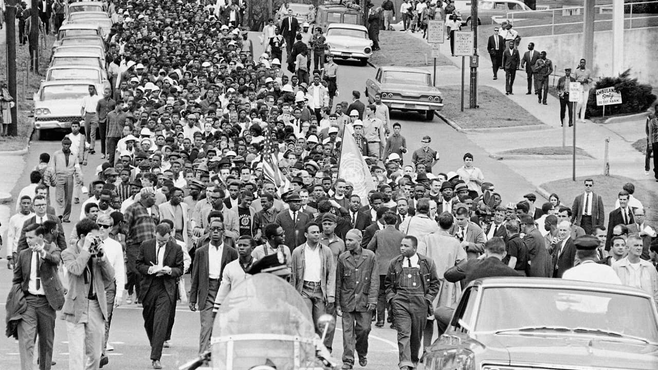 Photo of demonstrators walking to the courthouse behind the Rev. Martin Luther King Jr. in 1965