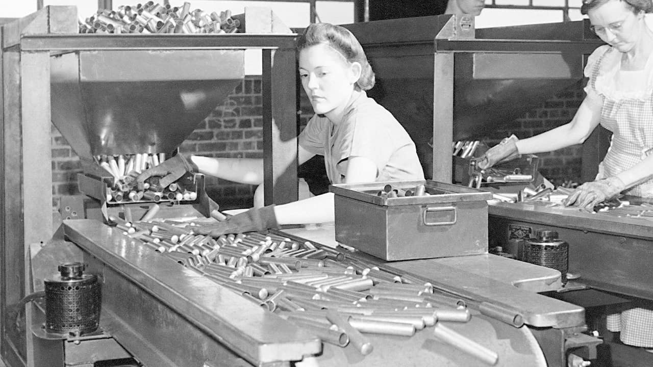 Photo of factory workers inspecting shell casings in 1942