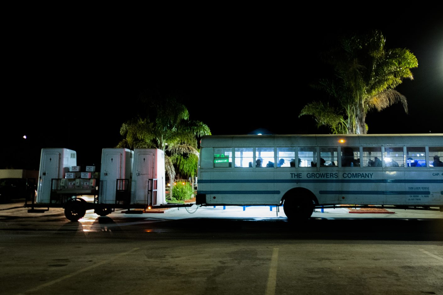 photo of farmworkers boarding bus at night